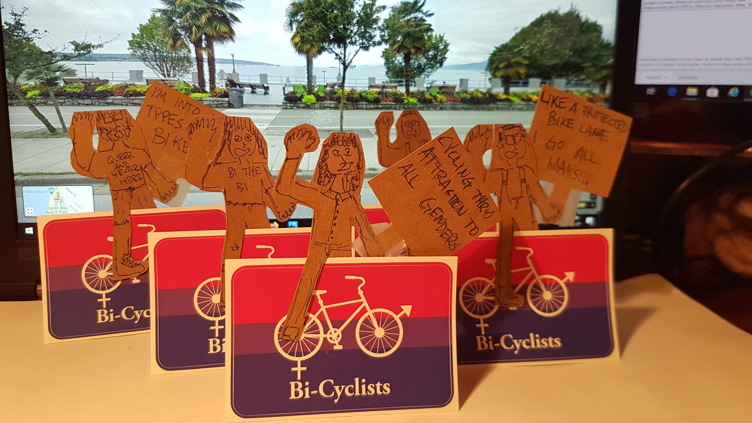 """A number of cardboard cutouts of people. The cutouts are placed on stickers that depict the bi flag and bicycles and the word """"Bi-Cyclists."""" The people are holding signs with slogans like """"Cycling through attraction to all genders"""""""