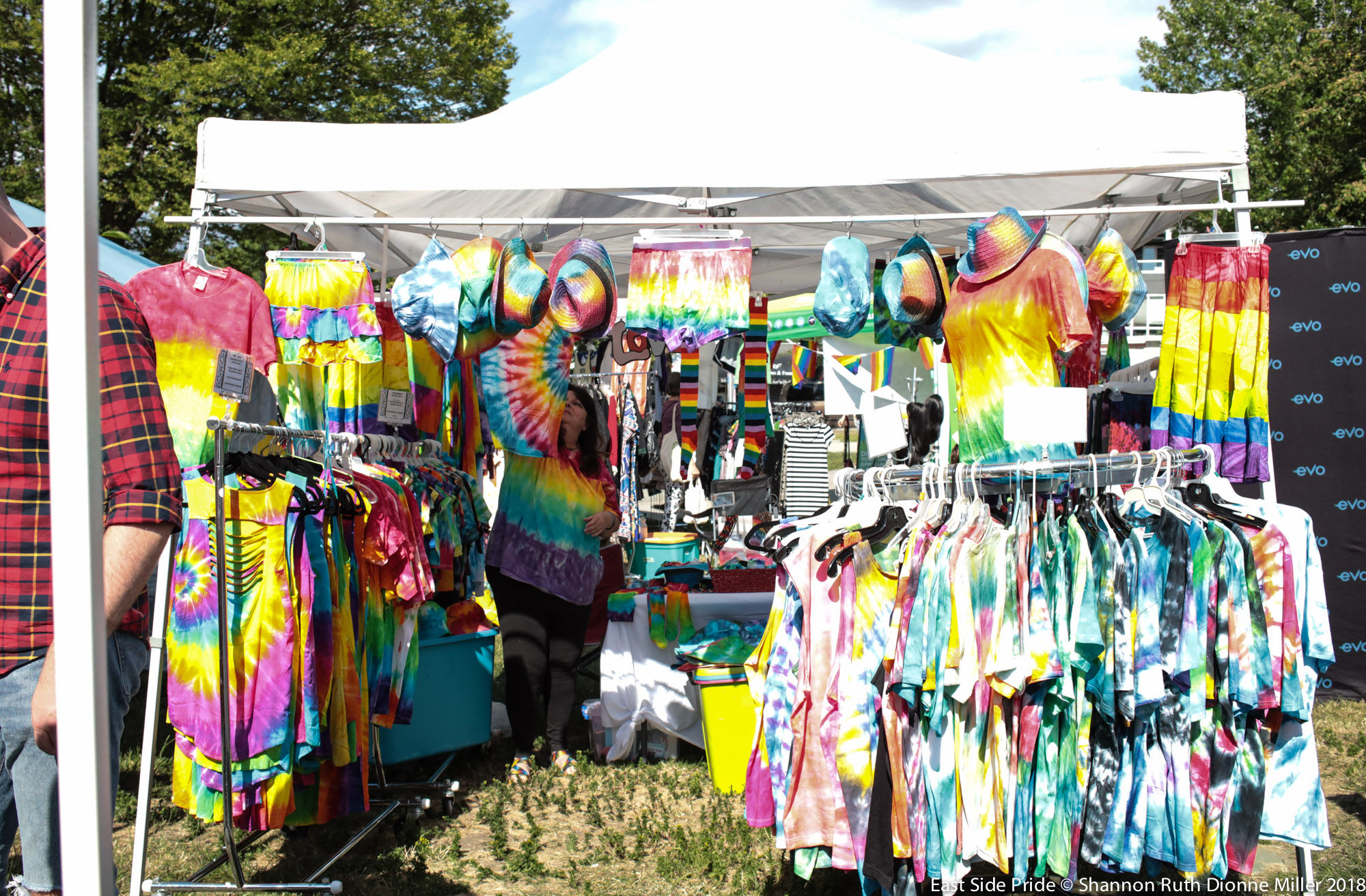 A vendor booth at East Side Pride 2018. The booth is outdoors under a white tent and is full of colourful tye dye outfits for sale.