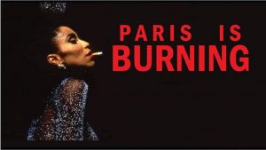 Poster for Paris is Burning. Image shows a Black person with a cigarette in their mouth, in a glitzy diamond covered outfit. The words Paris is Burning are in red.