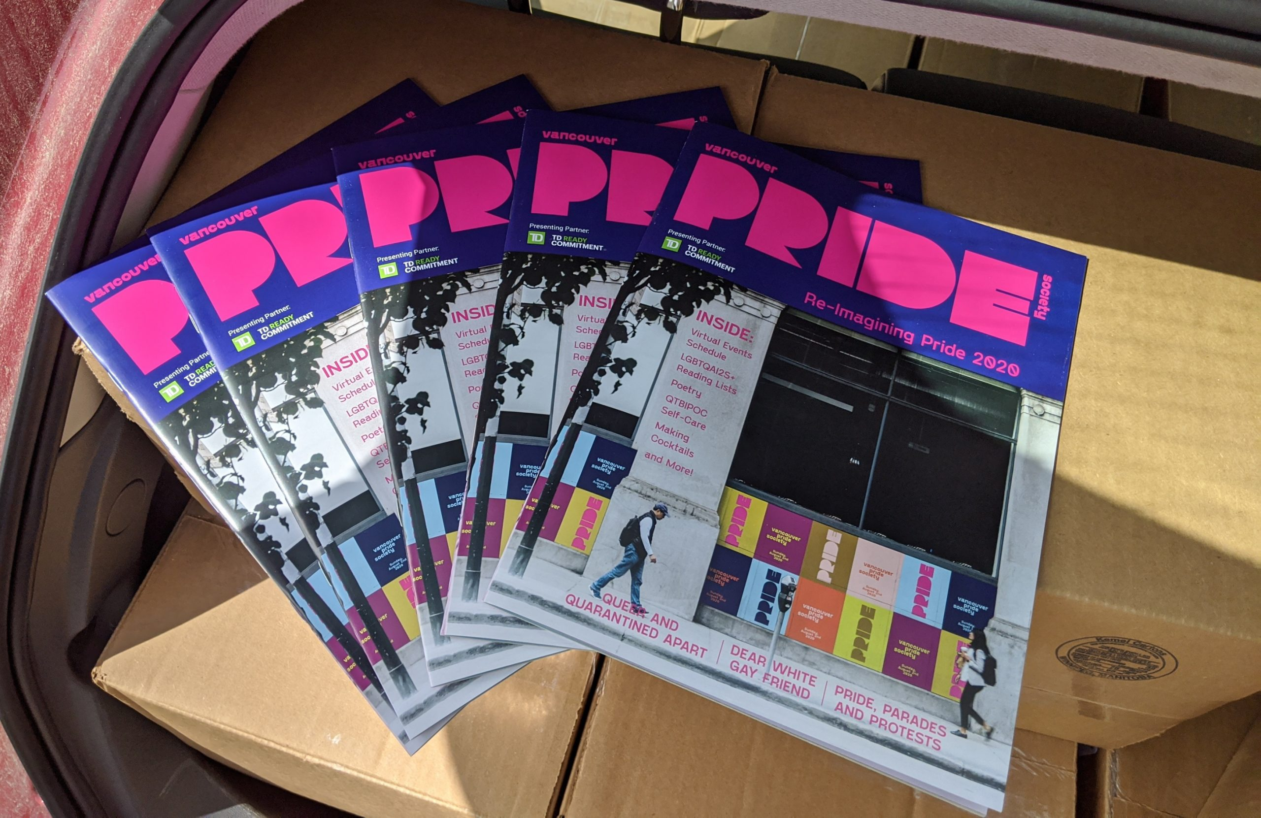 Several copies of Van Pride Magazine are fanned out on top of boxes in the back of a red vehicle.