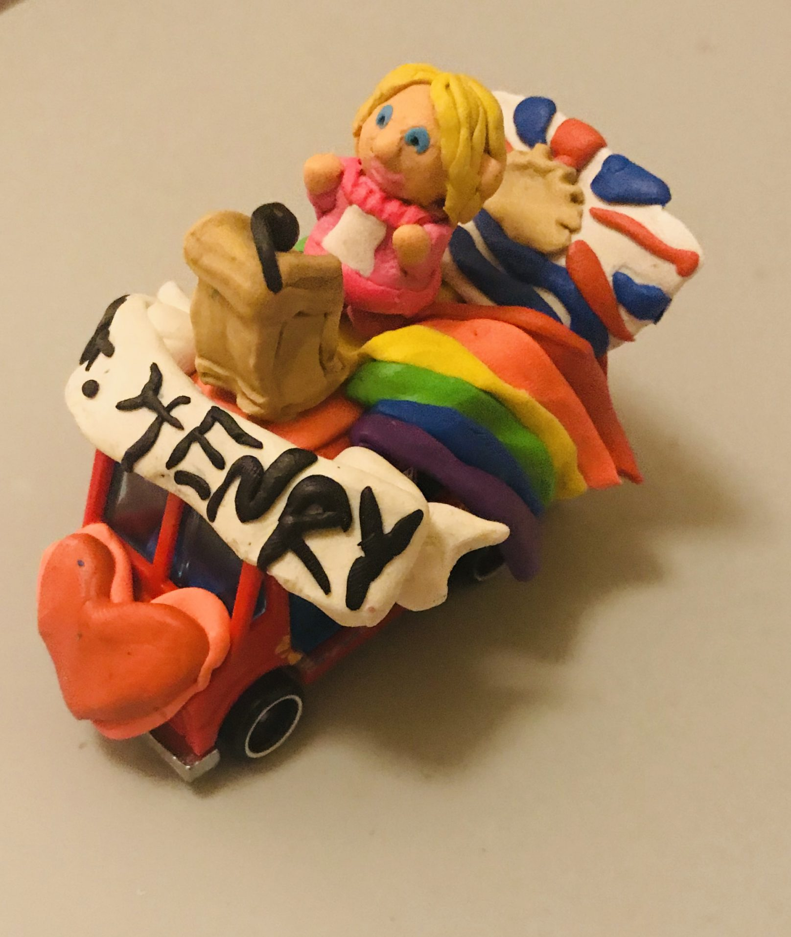 A mini parade float has been created out of clay encasing a toy car. A clay Bonnie Henry is standing at the top at a podium, with her name molded in black letters below. A rainbow and British Columbia flag are beside and behind her.