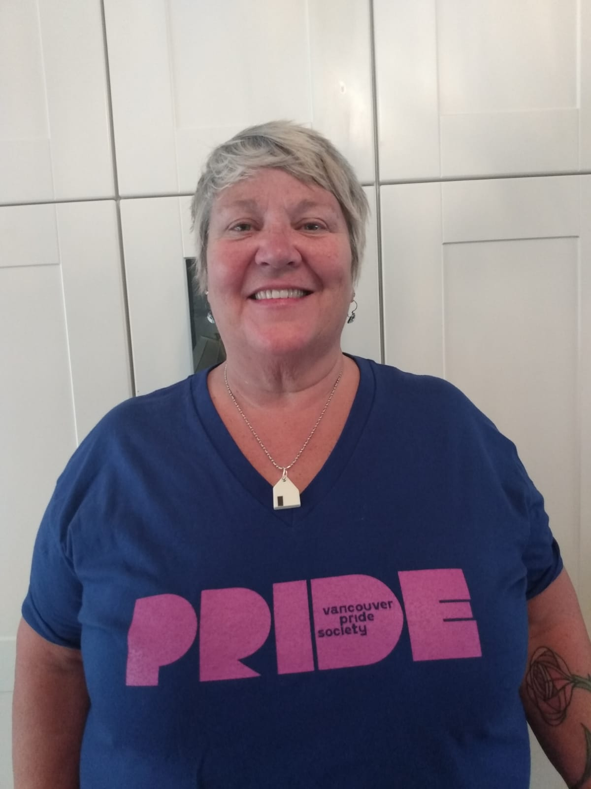 Michelle stands against a white wall and smiles at the camera. She has short grey hair, and is wearing a dark blue t-shirt with a light purple Vancouver Pride logo on it.