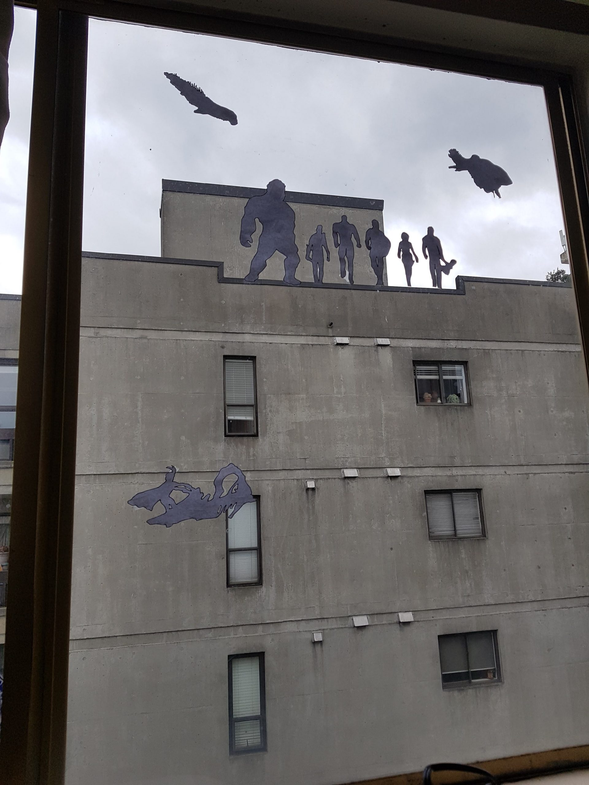 The image is shot from inside a building through a window. A concrete building is shown with the silhouettes of the Avengers standing on the roof.
