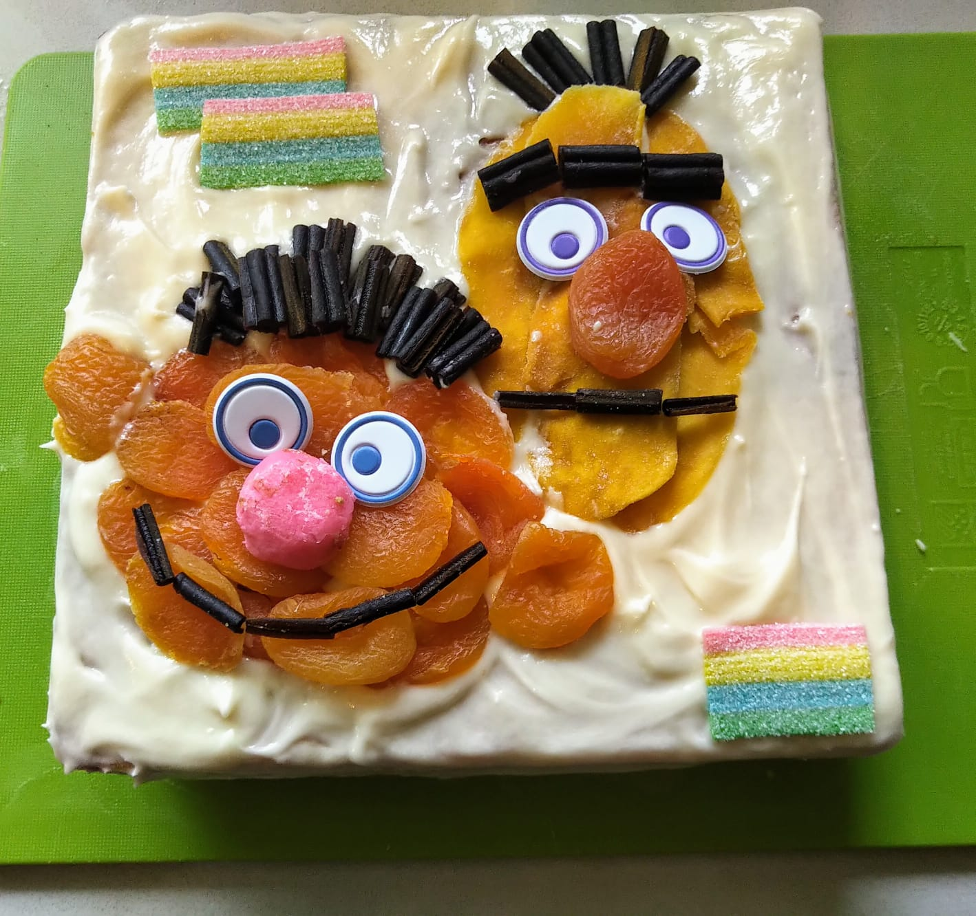 A square cake is shows with the faces of Sesame Street stars, Ernie and Bert, decorated in fruit and candy. The cake icing wis white and has candy rainbows in the corners.