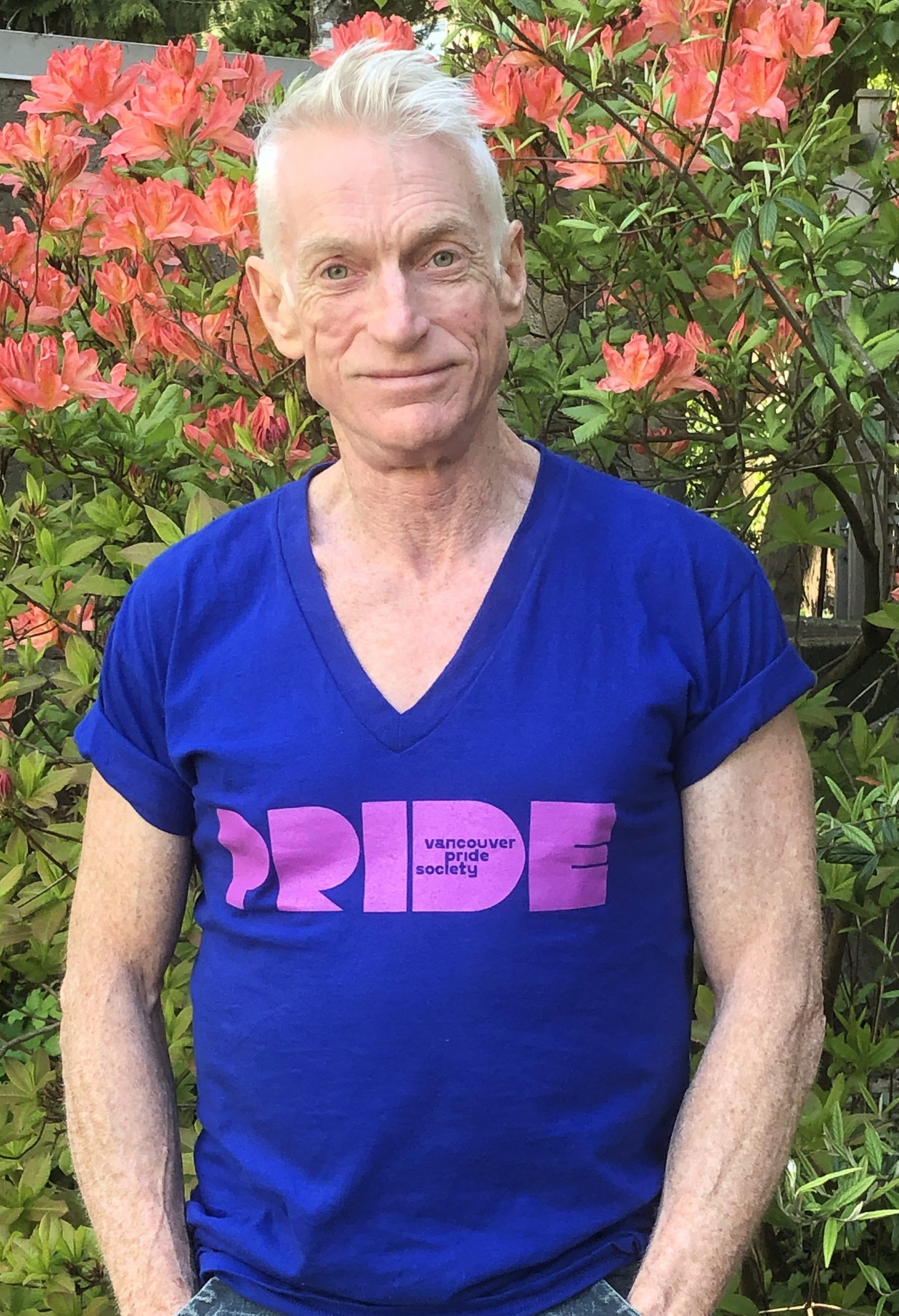 John stands in front of a pink flower bush and stares at the camera. He has short grey hair, and his armsare by his side. He is wearing a dark blue t-shirt with a purple Vancouver Pride logo on it