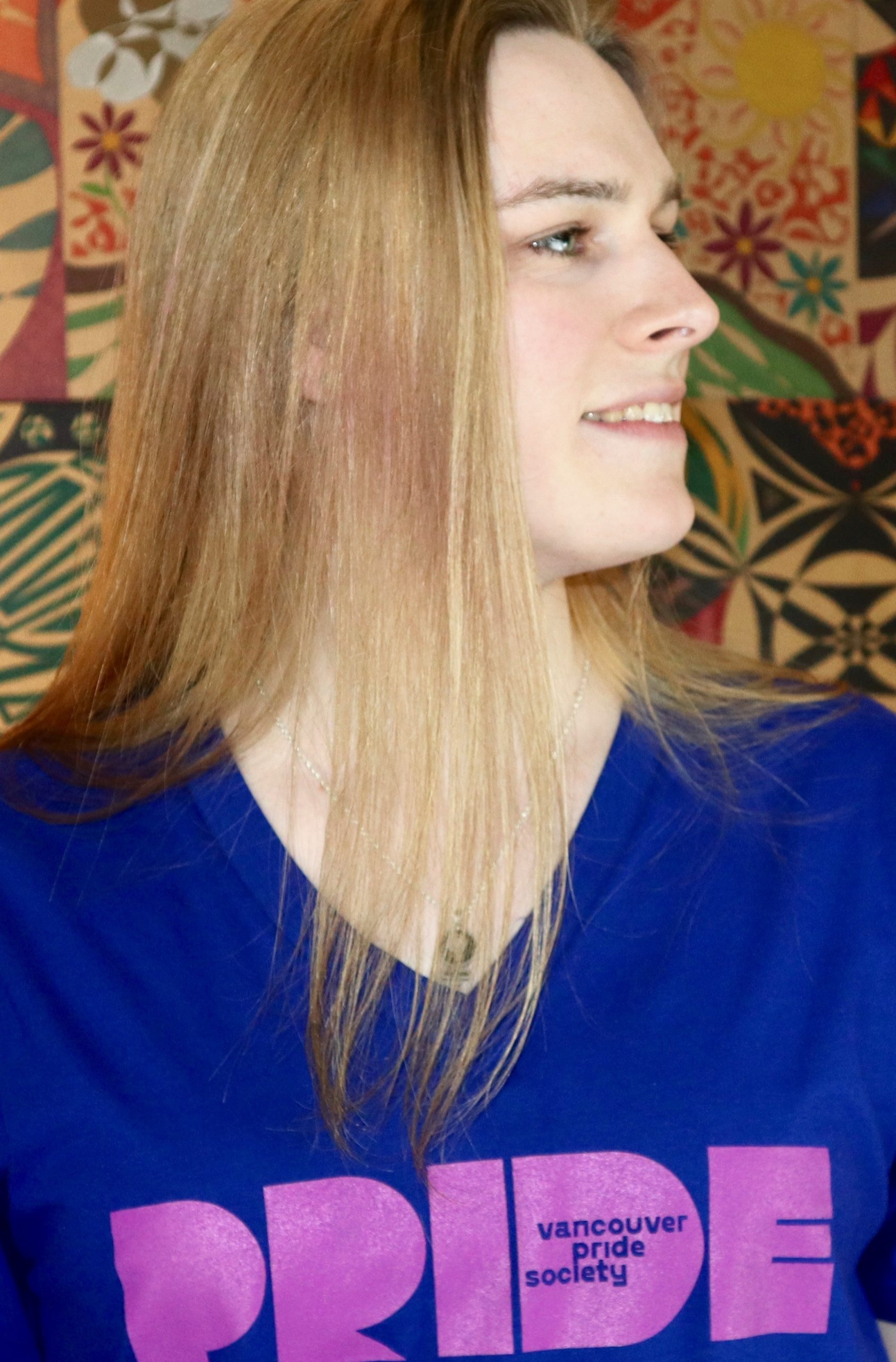 Nicola stands against a multi-coloured and patterned background and looks to her left. She has long blonde hair, and is wearing a dark blue t-shirt with a light purple Pride logo on it