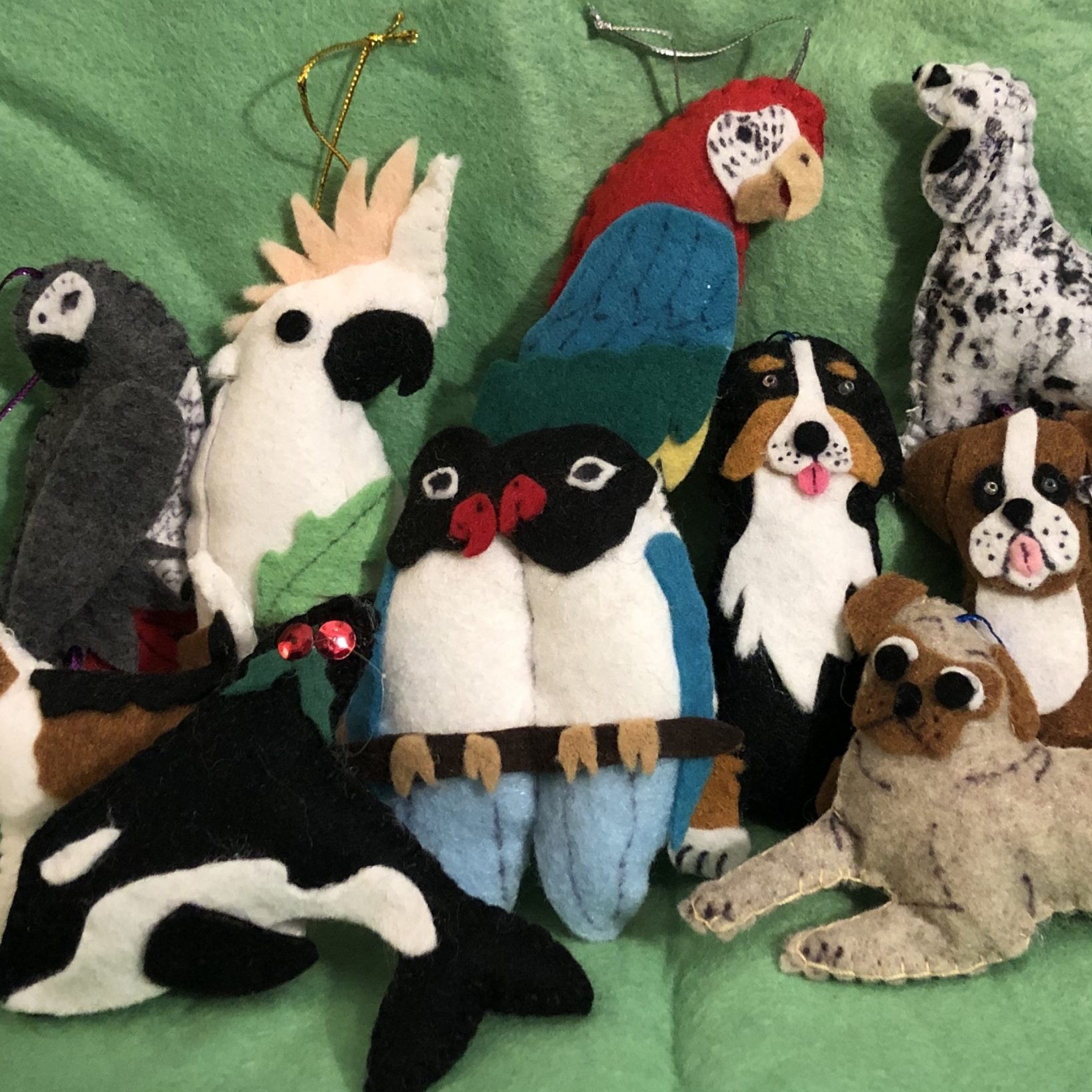 Various animals made out of felt are featured against a green backdrop. Most of the animals are birds, as there are multiple parrots, but there is also a killer whale and some dogs. Each animal has a string attached so it can be hung up as decoration.