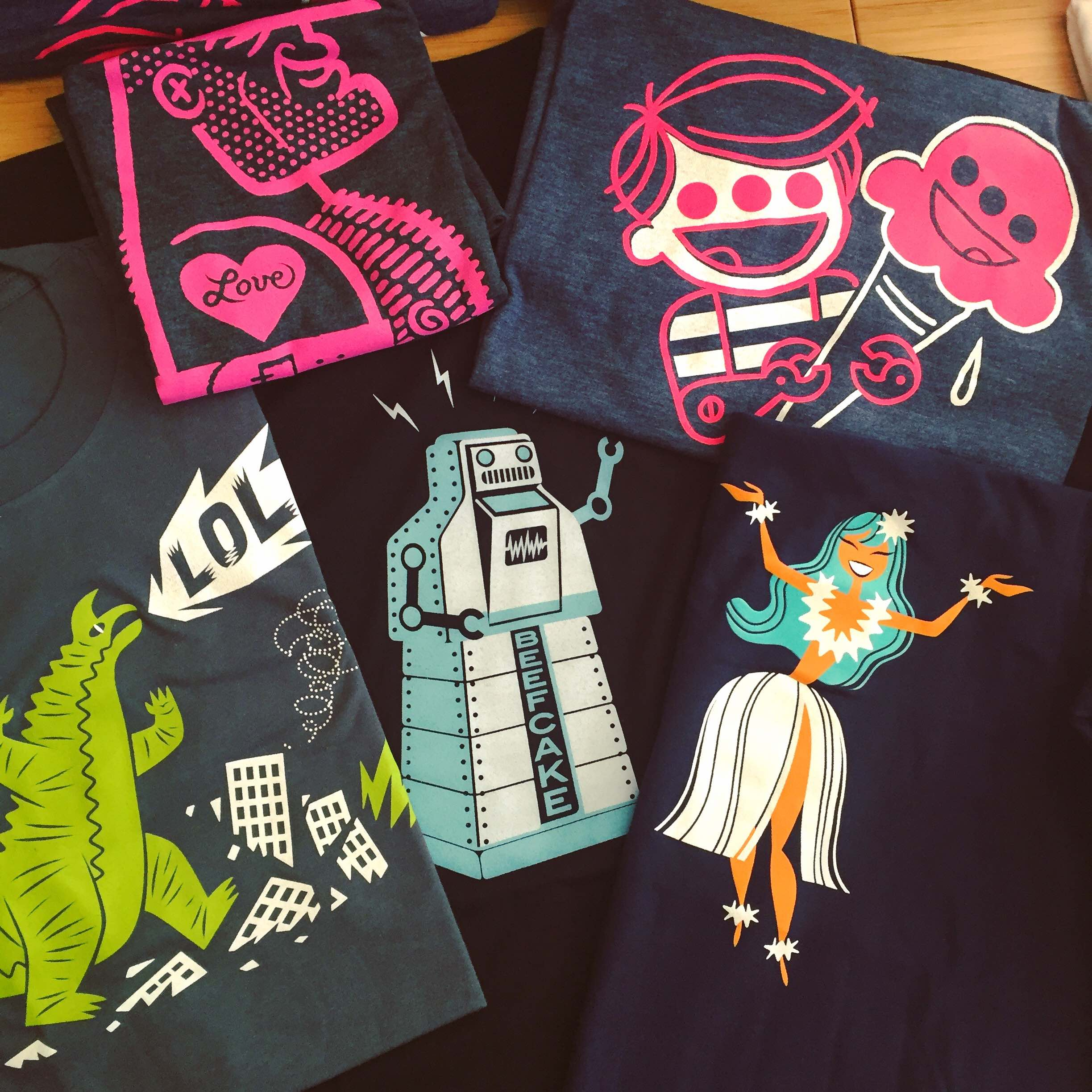 "Five printed black t-shirts are on a table. One has an image of a large robot on it, another has a bot with three eyes eating ice-cream, one shows Godzilla destroying a city with ""LOL'' in a soeech bubble, one shows a burly man with a heart tattoo on his arm and the last one shows a lady in a white dress with her arms raised"""