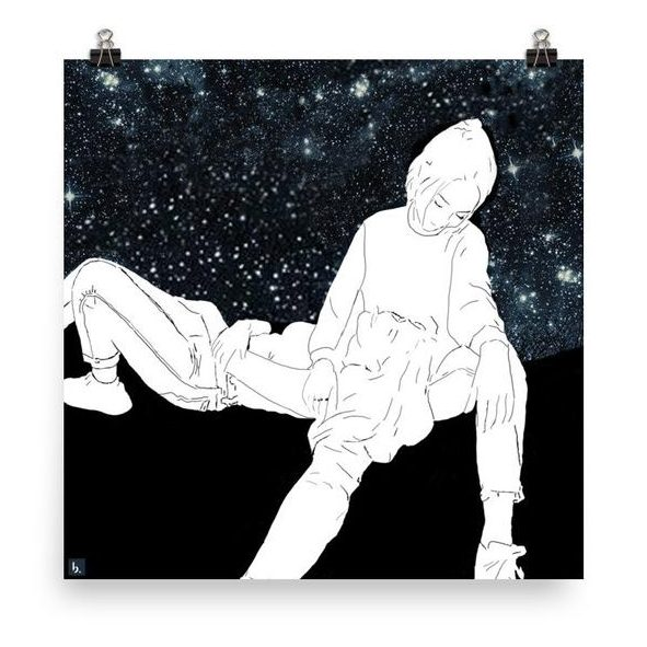 A black and white image is being held against a white backdrop with clips. In the image, a person is laying down with their head in another persons lap, looking up at the stars. The other person is looking down into the first persons eyes and smiling.