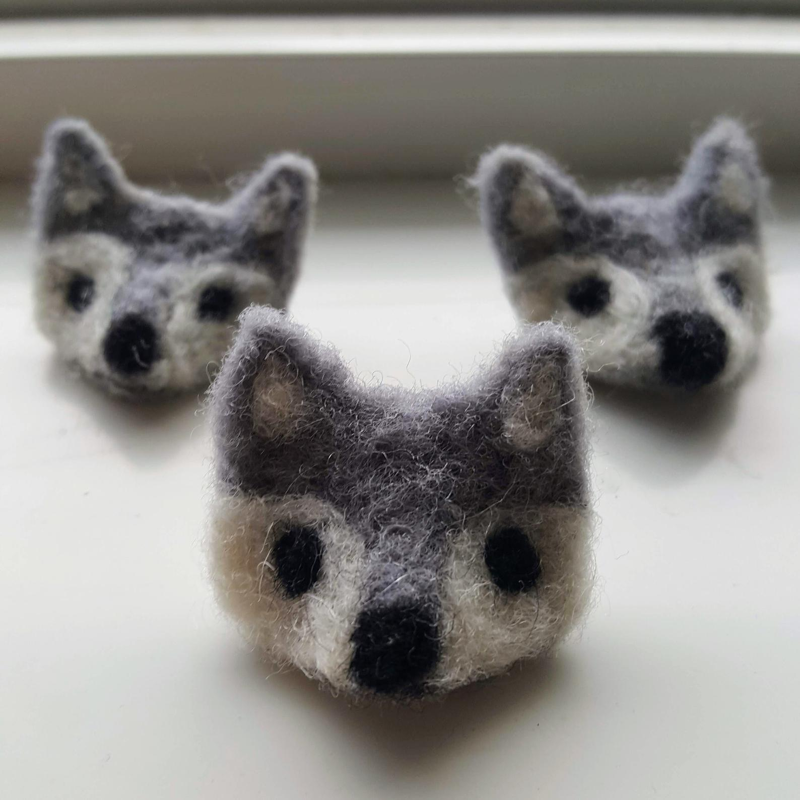 Three small grey wolf heads that are made out of felt. They have grey fur, which is white around the black eyes and nose. They are sitting on a windowsill.