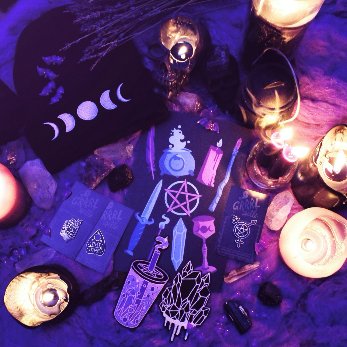 Various sinister objects are sitting on a table in the frame. Candles, itmes decorated with full moons, knives and 5 pointed stars etc. The lighting is dark and spooky