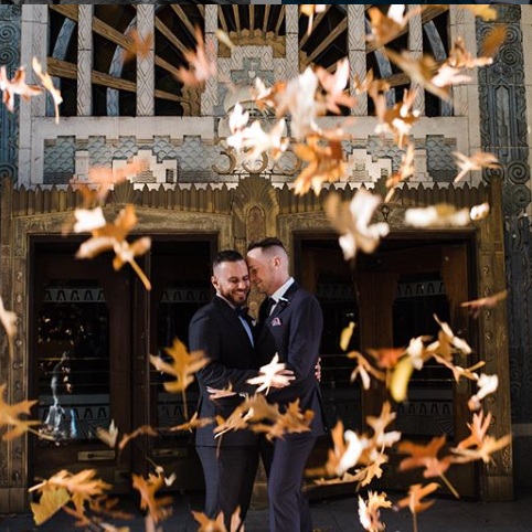 Two people in suits are being photographed outside of a regal-looking building. The people are smiling and embracing as if they have just gotten married. Leaves are falling through the air.