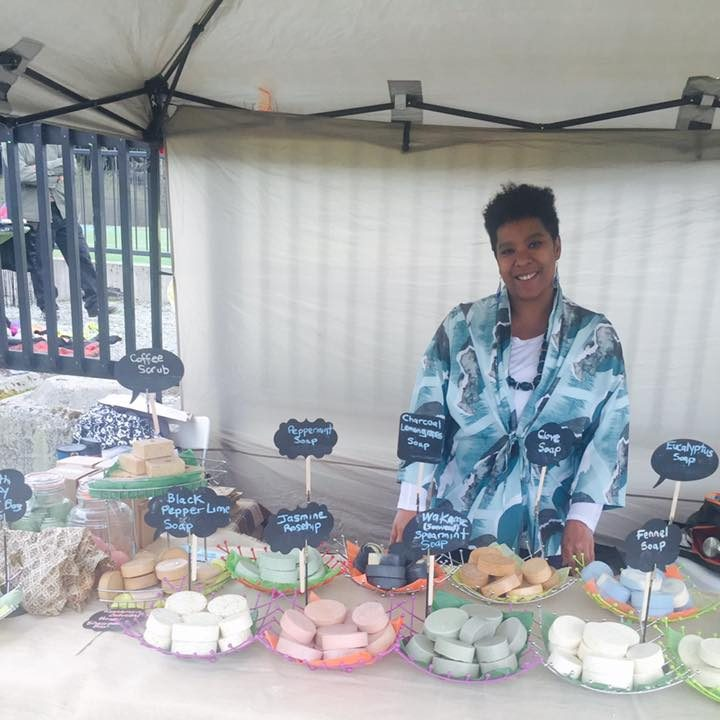 A person is smiling underneath a tent. They have varios plates of colourful, oval soap in front of the, that they appear to be selling at a market. The person has short, black hair and is wearing a colourful jacket.