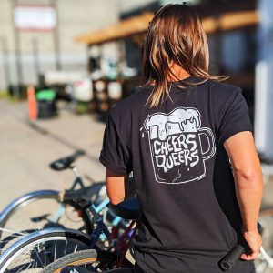 """A person is standing in front of a bicycle rack with their back to the camera. It is a bright and sunny day and a building is out of focus in the background. The person has shoulder length brown hair and is wearing a black t-shirt that has a graphic of a white beer mug with the words """"Cheers Queers"""" inside it."""