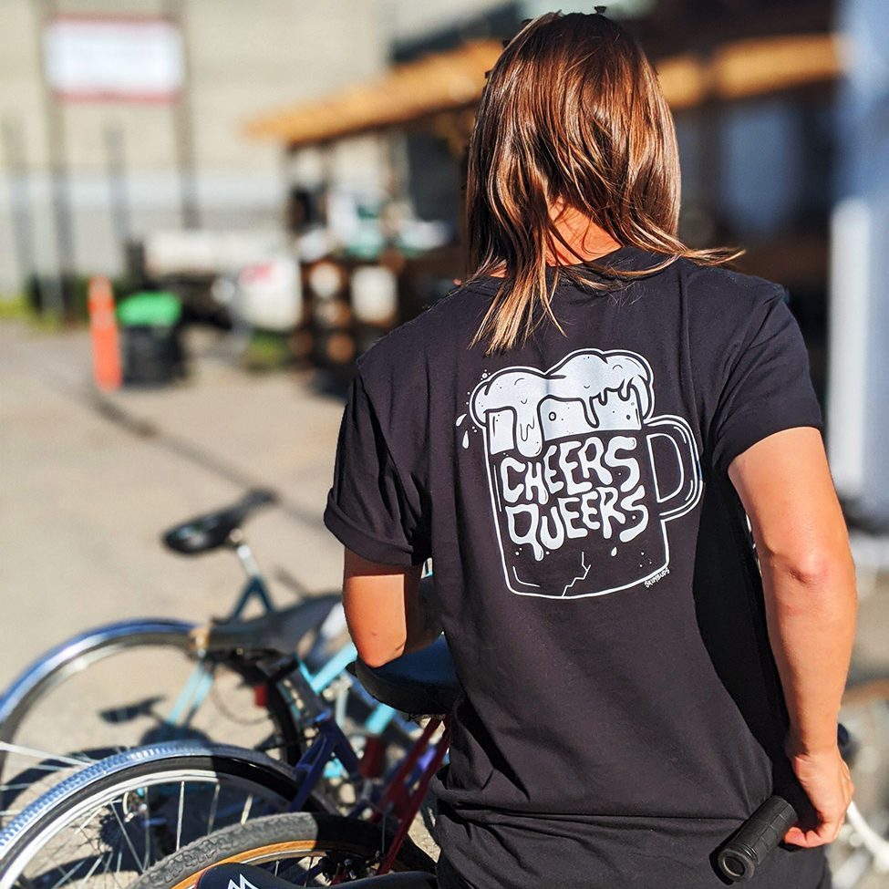 "A person is standing in front of a bicycle rack with their back to the camera. It is a bright and sunny day and a building is out of focus in the background. The person has shoulder length brown hair and is wearing a black t-shirt that has a graphic of a white beer mug with the words ""Cheers Queers"" inside it."