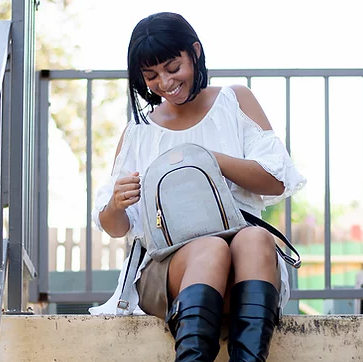 A person with a short bob and bangs is sitting on some steps in front of a window. They are wearing a white, over the shoulder top and are holding a white backpack with a golden zipper and black accents. They are smiling and looking into the bag.