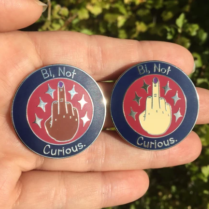 "A hand is holding two enamel pins. Both pins are circular and say ""Bi, Not Curious"". A hand with purple nail polish is in the center of the pin, with the middle finger up."