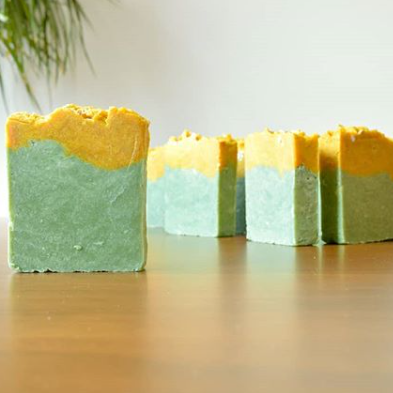 Multiple pieces of green soap with a yellow stripe on the top are sitting on a wooden table.