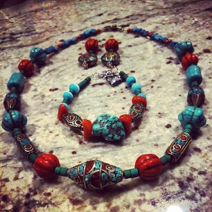Three pieces of jewelry are places on a marble countertop. The pieces are a necklace, earrings and a bracelet with the same red, blue and brown beaded design.