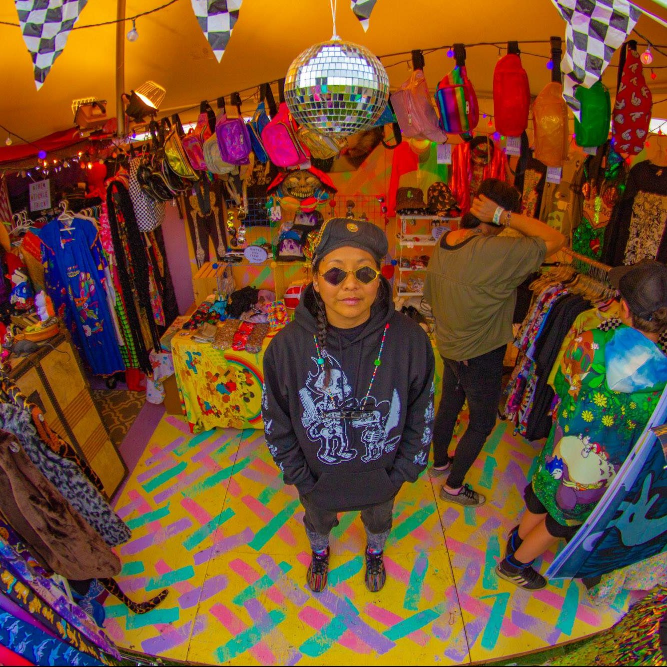 A person wearing sunglasses and a black hoodie is standing in the crenter of the frame. They are in a tent thats walls are lined with colourful ravewear. The floor is a colourful patterned carpet. A disco ball and checkered flags hang above their head.
