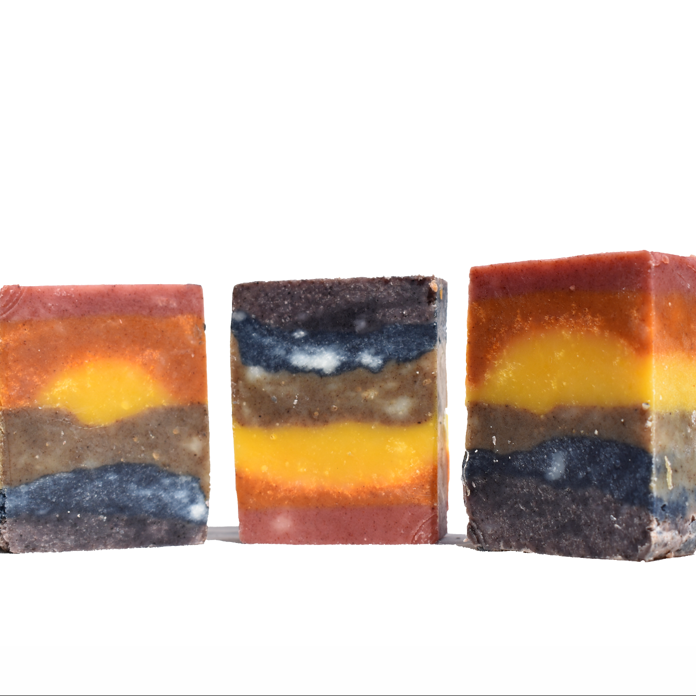 Three rectangular bars of soap are placed on a white background. The soaps are striped and multicoloured.