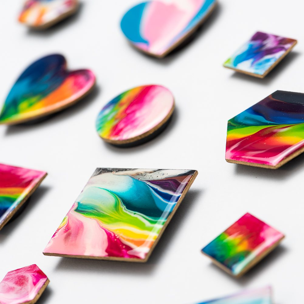 Many hand painted magnets are sitting on a white surface. The magnets are all different shapes, for example hearts, hexagons, circles and various sizes of squares. The magnets are all rainbow coloured.