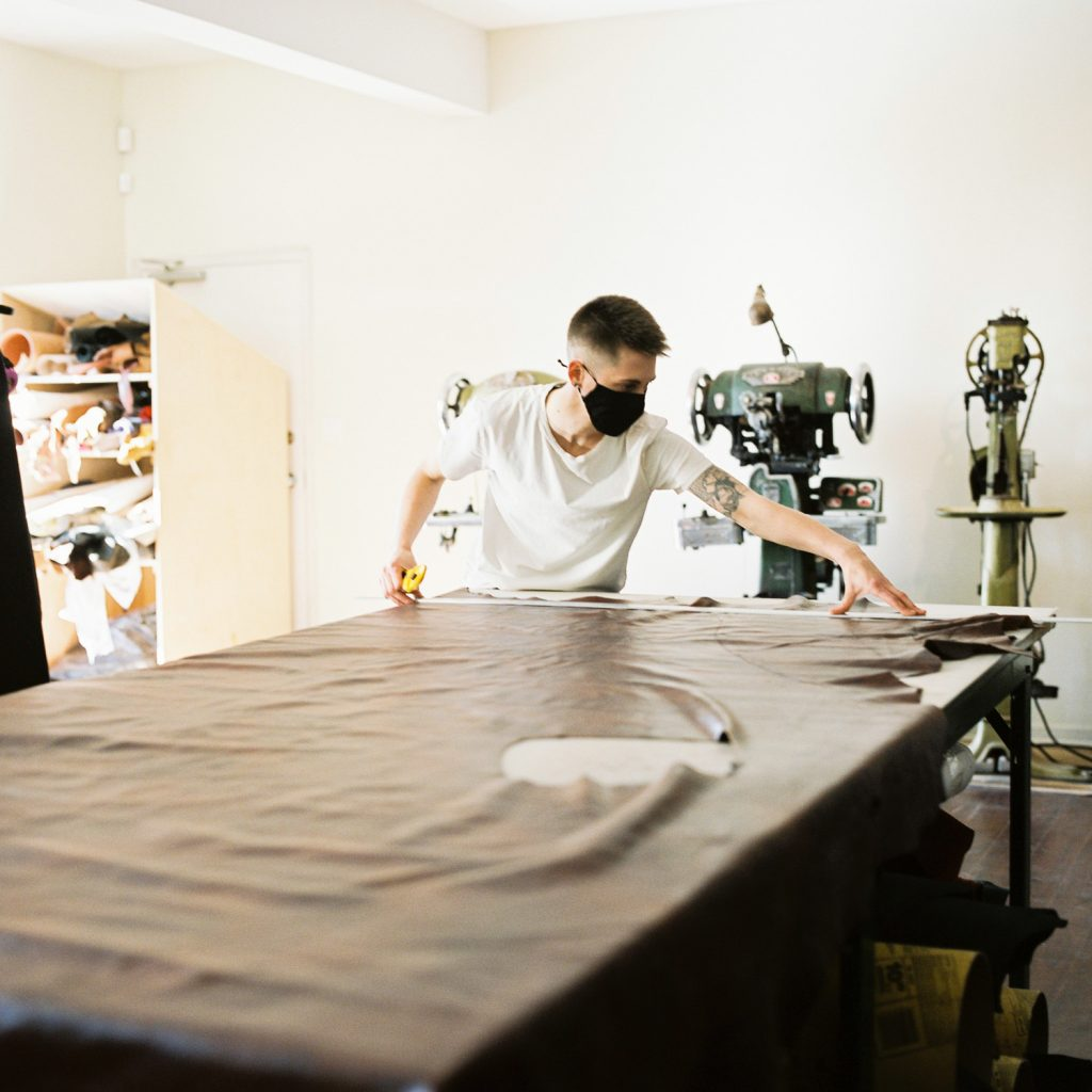 A person with short dark hair is measuring a large brown piece of leather on a long table.